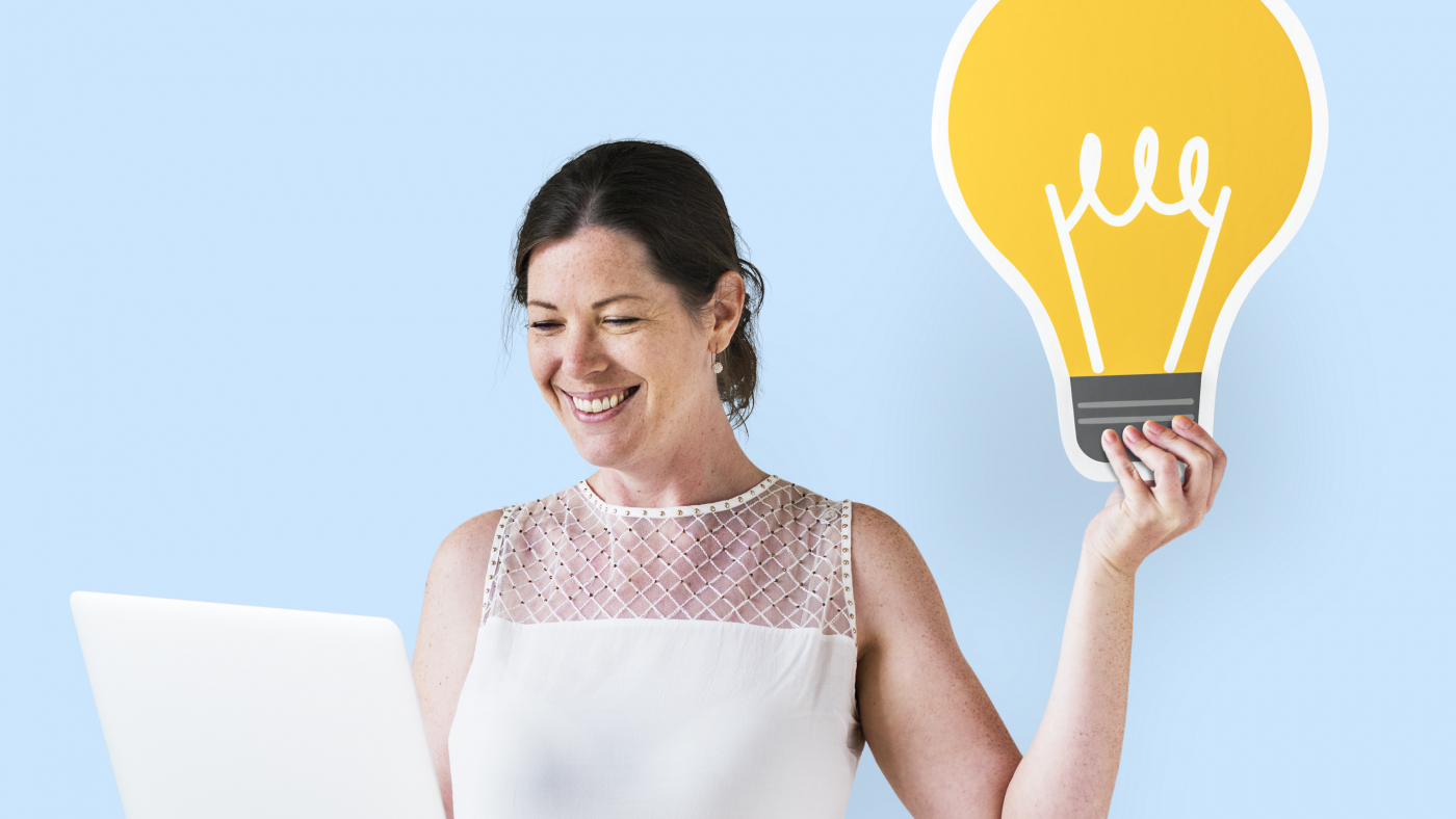 Woman holding an idea icon and using a laptop