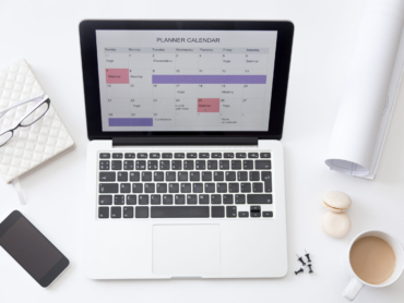 High angle view image of a working desk. Open laptop on the desk with a planner calendar on the screen. Business concept photo, close up