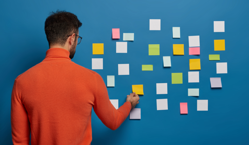 Back view of male professional works puts his ideas on stick notes, going to write main info for creating business plan wears bright orange jumper isolated on blue background. Education, office, work