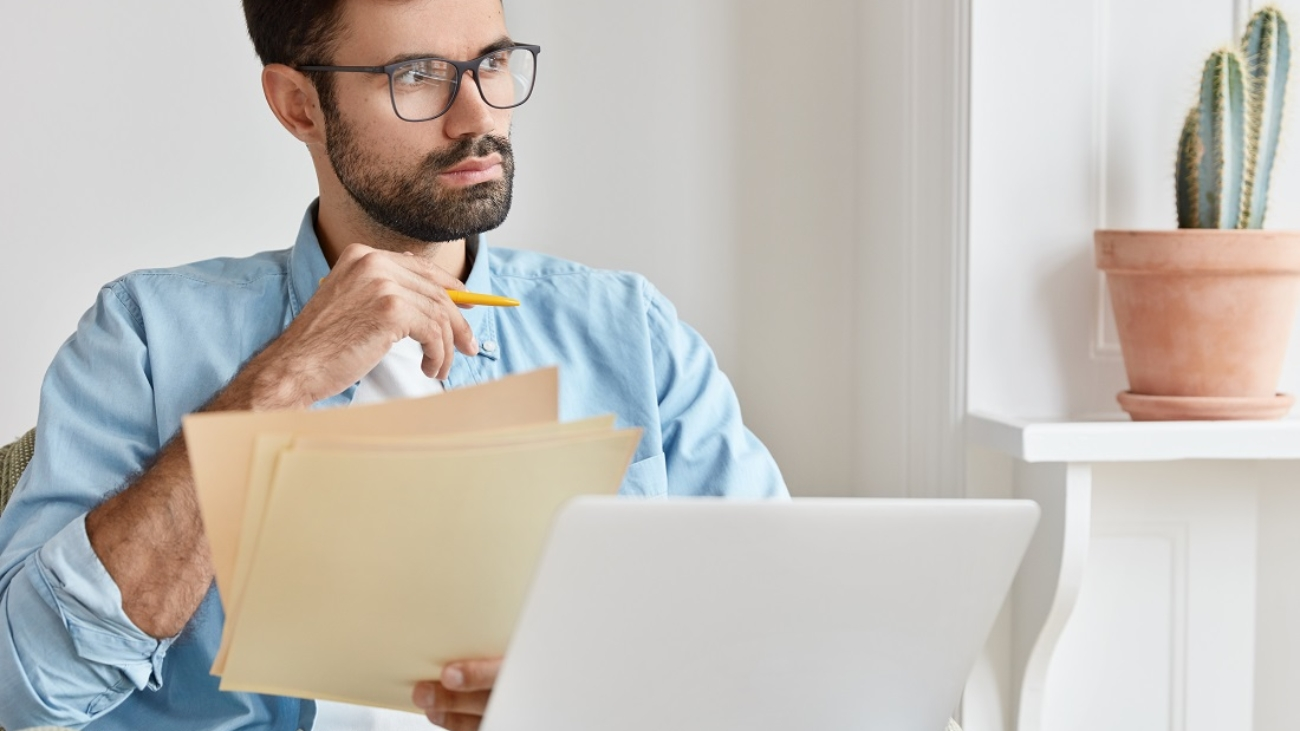 Bearded pensive man works from home, counts financial data, holds paper documents, uses laptop computer for searching information, wears glasses, concentrated aside, develops startup project