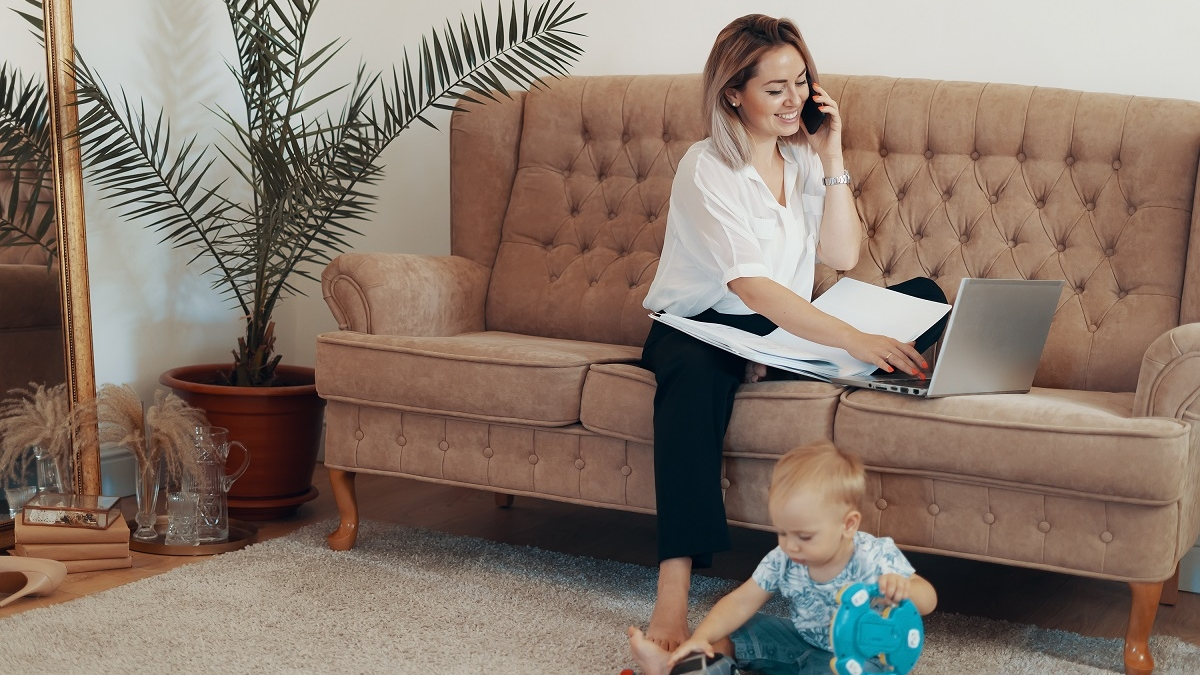 Beautiful business woman working at home. Multi-tasking, freelance and motherhood concept. Working mother career